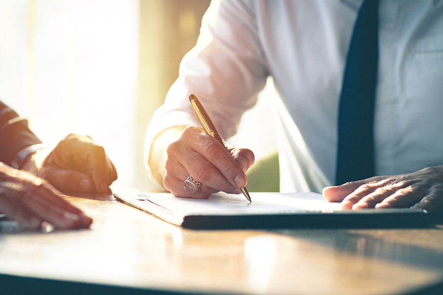 Medical Bill Review - Man Reviewing and Signing Medical Paperwork